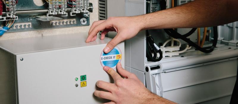 Elektrotechnik Hirschi aus Herne klebt die E-check plakette auf einen Sicherungskasten